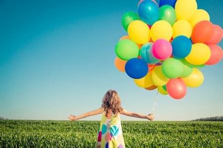 Gelukkig kind spelen met ballonnen buiten. Kind plezier in het voorjaar veld