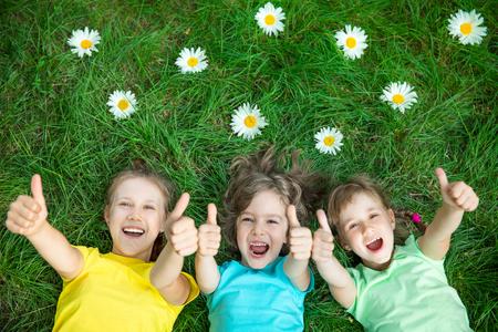 Groep gelukkige kinderen buiten spelen. Kinderen plezier in het voorjaar park. Vrienden liggend op het groene gras. Bovenaanzicht portret