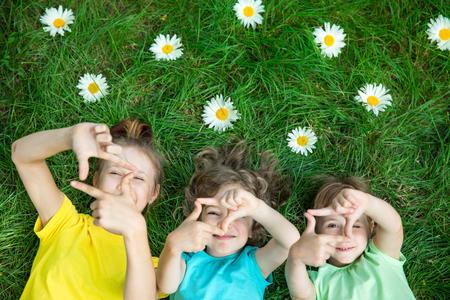 Grupo de niños felices jugando al aire libre. Niños que se divierten en el parque de la primavera. Amigos tirado en la hierba verde. Vista superior retrato Foto de archivo - 72384993
