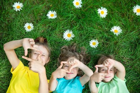 Group of happy children playing outdoors. Kids having fun in spring park. Friends lying on green grass. Top view portrait