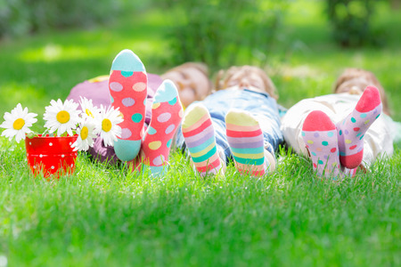 Group of happy children playing outdoors. Kids having fun in spring park. Friends lying on green grass Stock Photo - 72360323