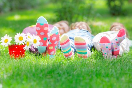 Gruppe glückliche Kinder spielen im Freien. Kinder, die Spaß im Frühjahr Park. Freunde, die auf grünem Gras liegen