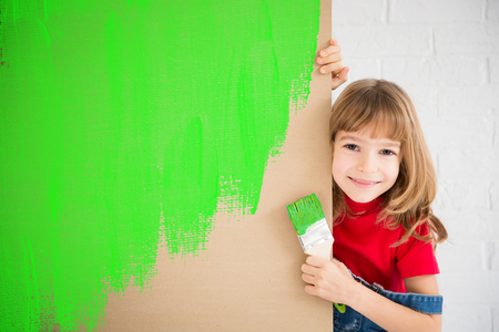 painting: Happy child painting recycle symbol on cardboard. Funny girl playing at home. Spring renovation and design concept Stock Photo