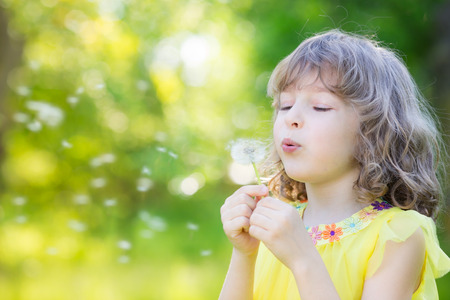 Happy child blowing dandelion flower outdoors. Girl having fun in spring park. Blurred green background. Dream and imagination concept Stock Photo