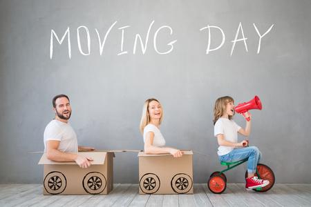 Familia feliz que juega a nuevo hogar. Padre, madre e hijo se divierten juntos. Mueve la casa día y el concepto de entrega urgente Foto de archivo - 73005746