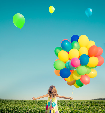 Happy child playing with bright multicolor balloons outdoor. Kid having fun in green spring field against blue sky background. Summer vacation and travel concept
