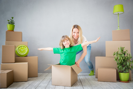 delivery room: Happy family playing into new home. Mother and child having fun together. Moving house day and express delivery concept Stock Photo