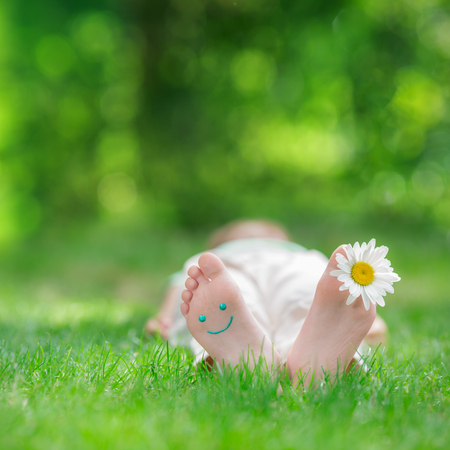 Happy feet with daisy flower outdoors. Kid having fun in spring park. Child lying on green grass. Ecology concept