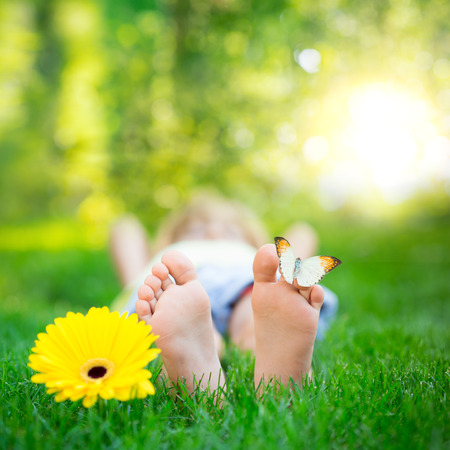 beautiful feet: Child lying on green grass