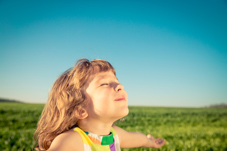 aspirational: Happy child outdoors against blue sky .