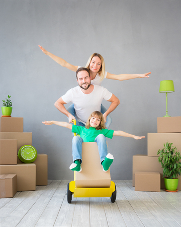 Happy family playing into new home. Father, mother and child having fun together. Moving house day and express delivery concept Standard-Bild