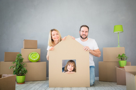 Familia feliz que juega a nuevo hogar. Padre, madre e hijo se divierten juntos. Mueve la casa día y el concepto de bienes raíces Foto de archivo - 73006028