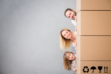 Het gelukkige familie spelen in het nieuwe huis. Vader, moeder en kind plezier samen. Bewegende dag huis en onroerend goed concept