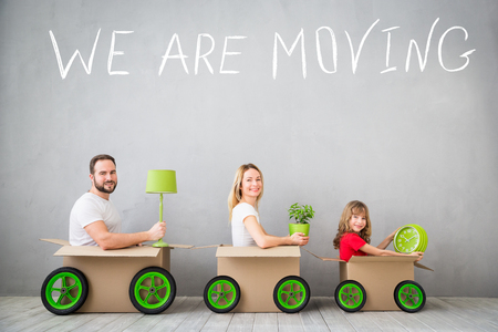 Happy family playing into new home. Father, mother and child having fun together. Moving house day and express delivery concept Stockfoto