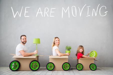 Het gelukkige familie spelen in het nieuwe huis. Vader, moeder en kind plezier samen. Bewegende dag huis en express-concept