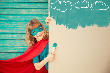 Superhero child painting the wall with blue color. Kid having fun at home. Spring renovation concept Foto de archivo