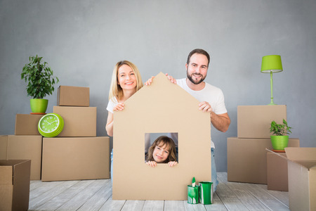 caras felices: Familia feliz que juega a nuevo hogar. Foto de archivo