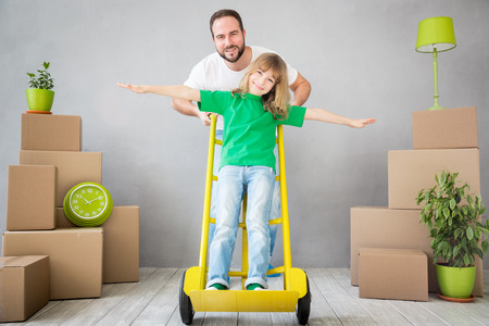 apartment: Happy family playing into new home. Father and child having fun together. Moving house day and express delivery concept Stock Photo