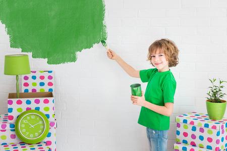Niño feliz que pinta la pared con color verde. Cabrito que se divierten en el hogar. concepto de actualización de primavera Foto de archivo