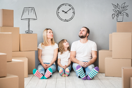 Happy family playing into new home. Father, mother and child having fun together. Moving house day and real estate concept Stock Photo