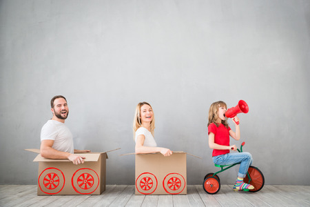 Happy family playing into new home. Father, mother and child having fun together. Moving house day and express delivery concept Archivio Fotografico