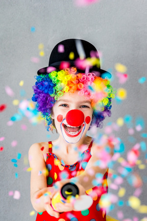 Bang! Funny kid clown playing at home. Child shooting party popper confetti. 1 April Fool's day concept Archivio Fotografico