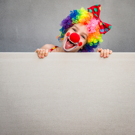 Funny kid clown. Child holding banner blank. 1 April Fools day concept