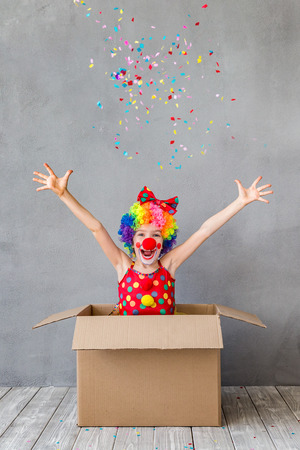 Funny kid clown in cardboard box. Child playing at home. 1 April Fools day concept