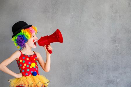 Funny dzieciak clown. Dziecko rozmowie z megafonem. koncepcja dzień 1 Prima Aprilis
