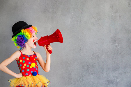 Funny kid clown. Child speaking with megaphone. 1 April Fool's day concept Foto de archivo
