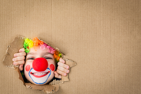 Funny kid clown looking through hole on cardboard. Child playing at home. 1 April Fools day concept. Copy space. Stock Photo