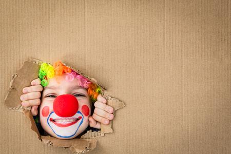 Funny kid clown op zoek via gat op karton. Spelen van het kind thuis. 1 april Fool's Day concept. Kopieer ruimte.