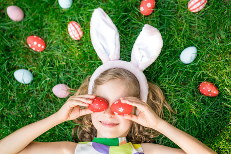 traditional: Easter bunny. Child having fun outdoor. Kid playing with eggs on green grass. Spring holidays concept Stock Photo