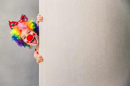 Funny kid clown. Child holding banner blank. 1 April Fool's day concept Foto de archivo