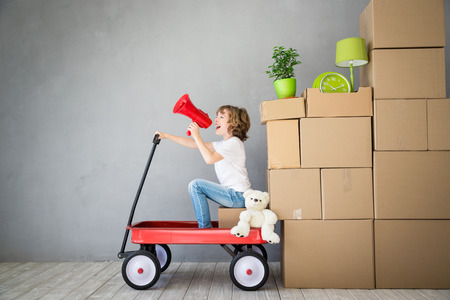 1 person: Happy child playing into new home. Kid having fun indoor. Moving house day and express delivery concept Stock Photo