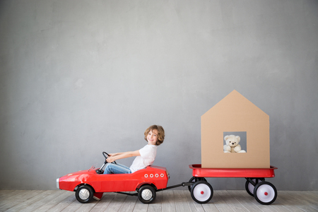 Happy child playing into new home. Kid having fun indoor. Moving house day and express delivery concept Imagens