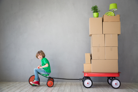 moving truck: Happy child playing into new home. Kid having fun indoor. Moving house day and express delivery concept Stock Photo