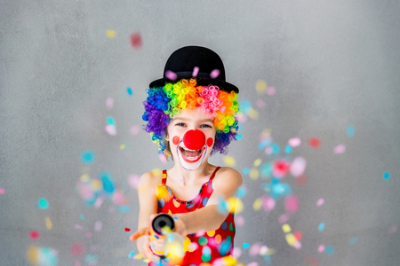Bang! Funny kid clown playing at home. Child shooting party popper confetti. 1 April Fool's day concept Foto de archivo