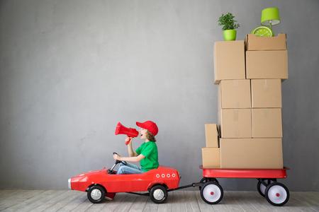 Glückliches Kind in neues Haus zu spielen. Kind Spaß indoor. Umzug Tag und Express-Lieferung Konzept