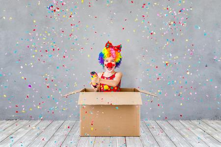 バン!面白い子供ピエロが自宅で再生します。子供撮影パーティー ポッパー紙吹雪。1 エイプリルフールの日の概念
