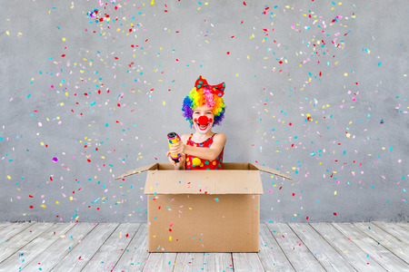 Bang! Funny kid clown playing at home. Child shooting party popper confetti. 1 April Fool's day concept 版權商用圖片