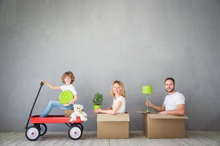 Happy family playing into new home. Father, mother and child having fun together. Moving house day and express delivery concept Banque d'images