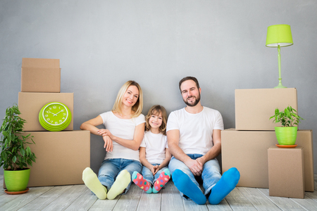 moving box: Happy family playing into new home. Father, mother and child having fun together. Moving house day and real estate concept Stock Photo