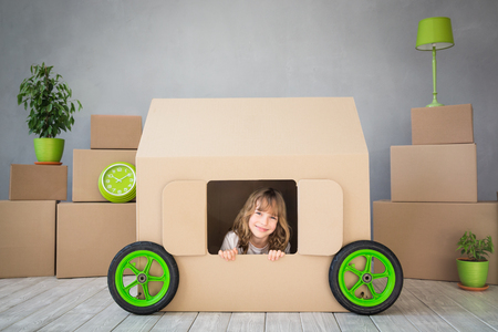 1 person: Happy child playing into new home. Moving house day and real estate concept