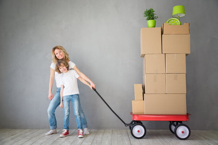 copyspace: Happy family playing into new home. Father, mother and child having fun together. Moving house day and express delivery concept Stock Photo