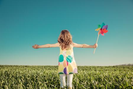 Felices del niño al aire libre contra el fondo del cielo azul. Cabrito que se divierte en el campo de primavera verde. La libertad y la imaginación concepto