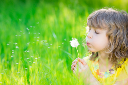 seed: Happy child blowing dandelion flower outdoors. Girl having fun in spring park. Blurred green background. Dream and imagination concept Stock Photo