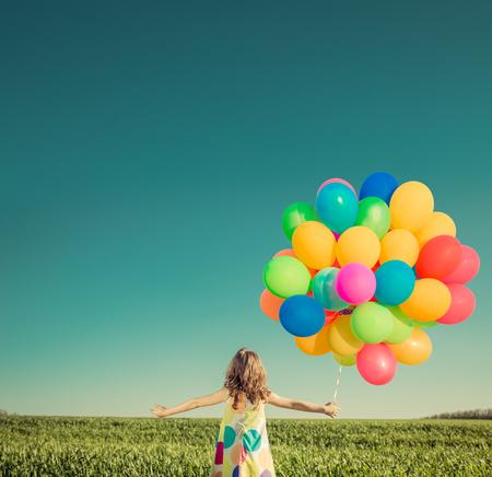 divercio n: Niño feliz que juega con los globos multicolores brillantes al aire libre. Cabrito que se divierte en el campo de primavera verde contra el cielo azul de fondo. vacaciones de verano y el concepto de viaje Foto de archivo