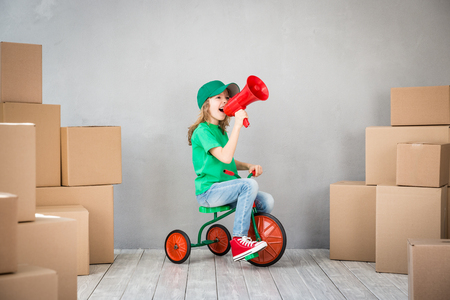 moving box: Happy child playing into new home. Kid having fun indoor. Moving house day and express delivery concept Stock Photo
