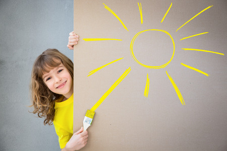 home decorating: Happy child painting the cardboard with yellow color. Kid having fun at home. Spring renovation concept Stock Photo